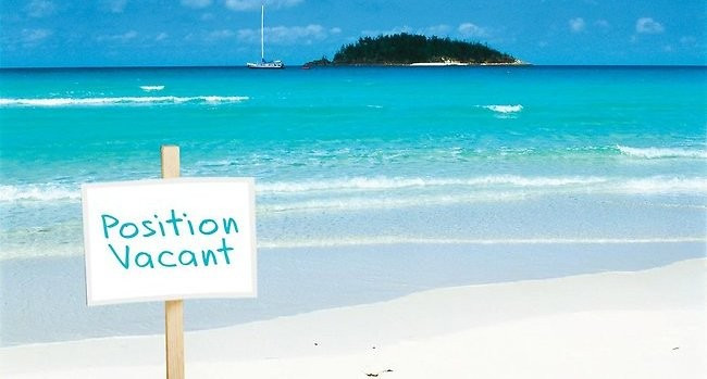 """Image of a tropical island and beach with a sign in foreground saying: """"position vacant"""""""