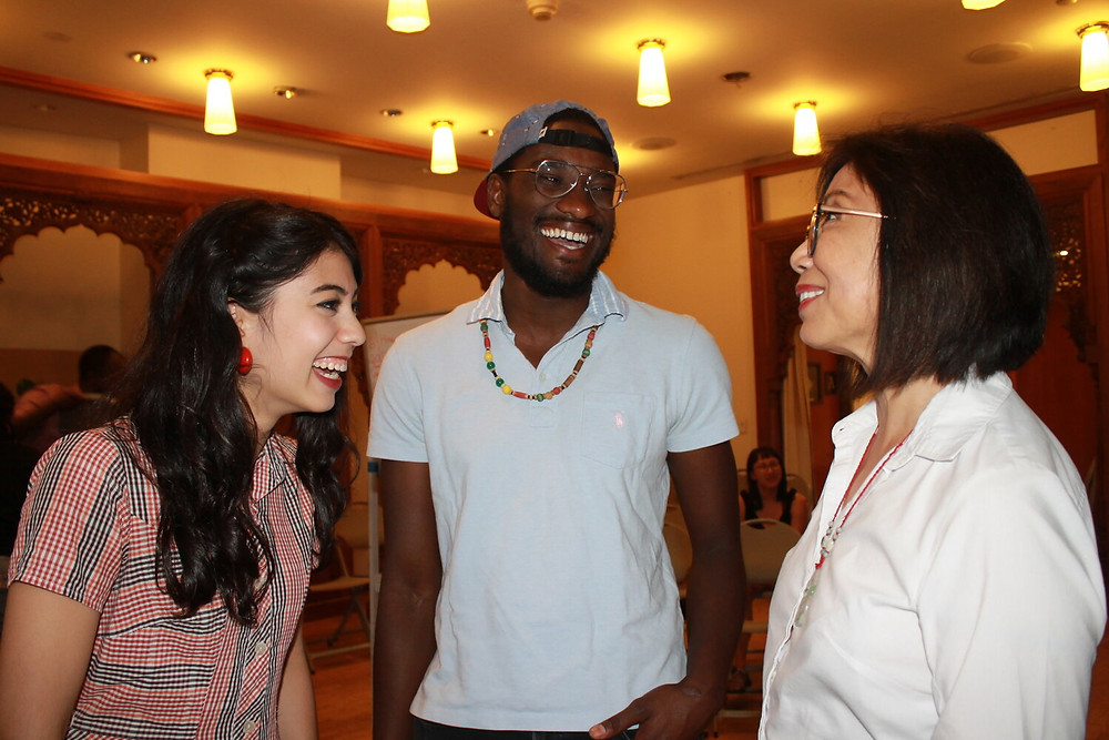Photo from Ammud.org that shows three people smiling and laughing together. Yehudah is in the center of the image.