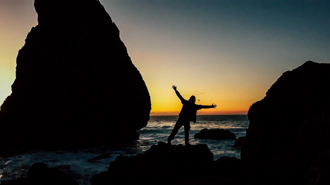 person-between-rocks-ocean-sintra-dusk.j