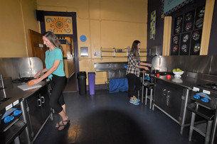 Two guests prepare meals in the fully equipped kitchen of Gaslamp Hostel San Diego