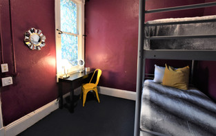 Private room with one bunk bed that includes a make up table and lighted mirror.