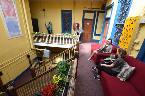 guests enjoy the open and sunny space of the third floor of the atrium at Gaslamp Hostel San Diego