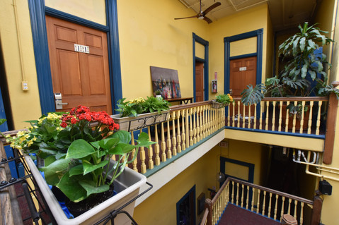 The third floor balcony is lined with colorful flowers and bright yellow and teal walls and accents