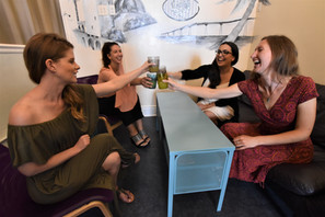 Four guests raise their glasses and have a laugh in the lounge of Gaslamp Hostel San Diego