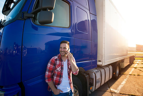 Truck driver standing by his truck and t