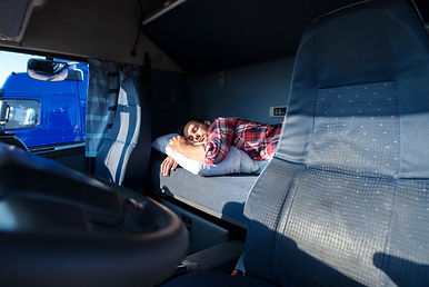 Truck driver sleeping on bed inside truc