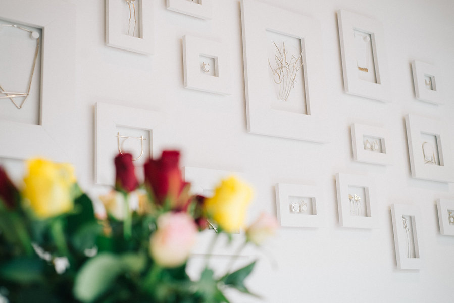 Mur de présentation du magasin,  cadre en bois blanc  ou sont exposer les bijoux.