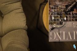 Detalhe de poltrona costela, uma lupa e uma revista living