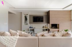 Sala de estar com sofá, televisão, lareira e painel em melamina cinza e amadeirada