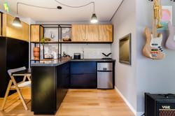 Cozinha estilo industrial com compensado naval e estrutura aparente em preto e balcões pretos