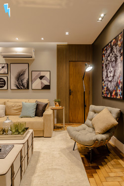 Sala de estar com poltrona costela, quadro de leão, luminária de chão, sofá e detalhe ripado ao fund