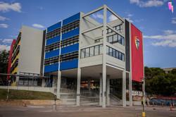 Perspectiva de fachada de escola em cinza e cores vibrantes
