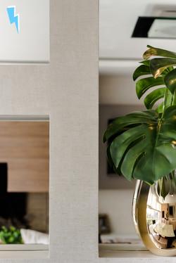 Detalhe de painel com espelho, melamina cinza e vaso dourado com costela de adão