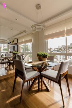 Mesa de jantar de vidro e cadeiras em madeira e estofado cinza