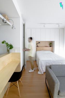 Pessoa abrindo armários em um loft, mostrando a sala, cozinha e o quarto