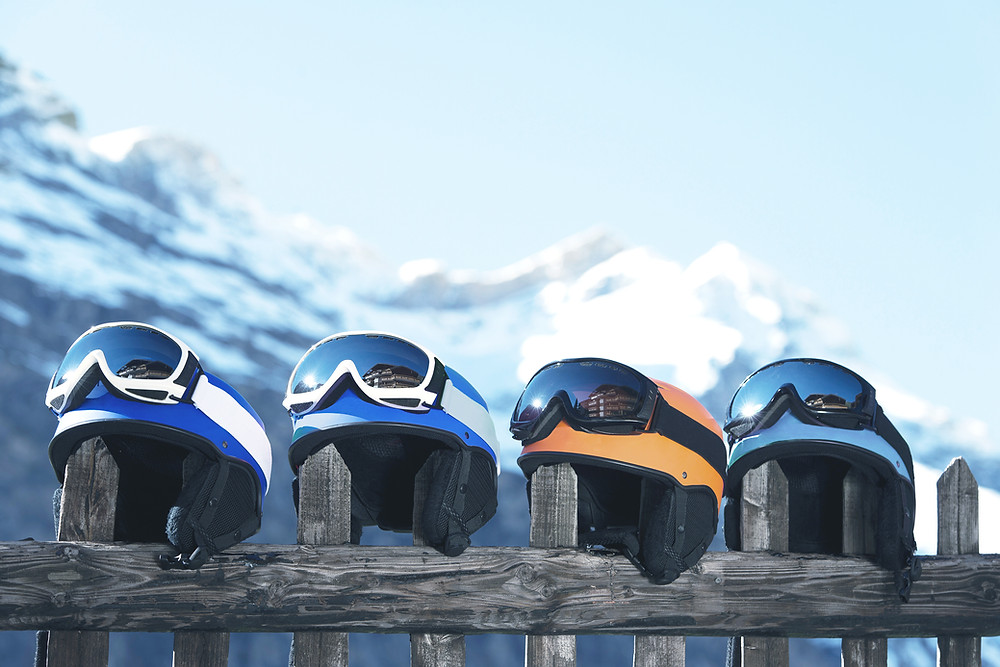 Ski helmets sitting on a rail in the mountains