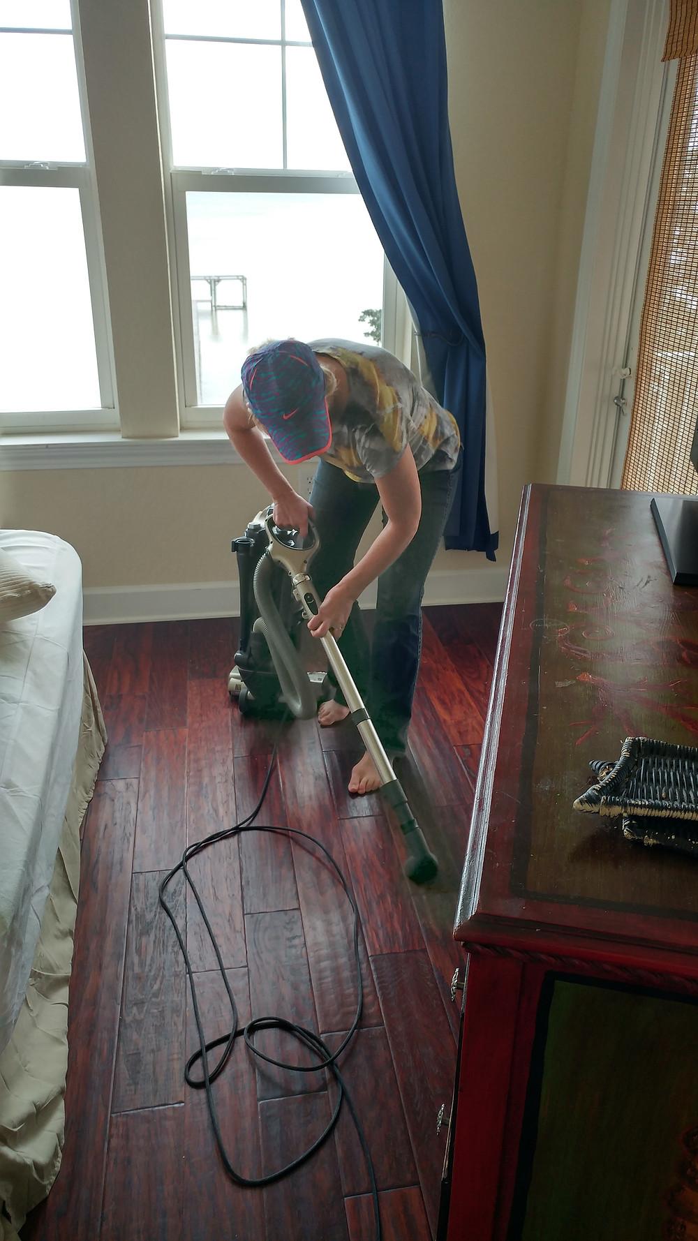 Elizabeth vacuums behind dresser.