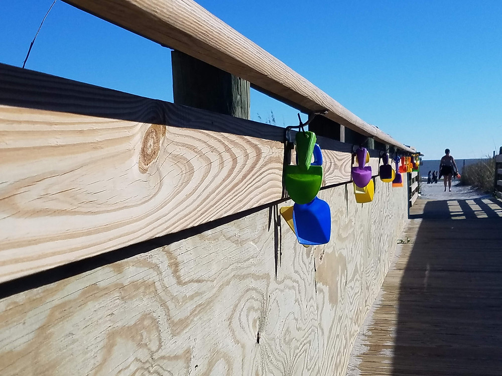 Walkway to beach is lined with courtesy beach toys for kids.