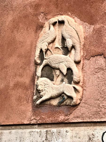 loseta de mármol que representa en la parte superior, dos pájaros enfrentados, y en la parte inferior un tercer pájaro con las patas levantadas, que parece estar golpeando a un león Foto: Giovanni.mello, CC BY-SA 4.0 <https://creativecommons.org/licenses/by-sa/4.0>, via Wikimedia Commons