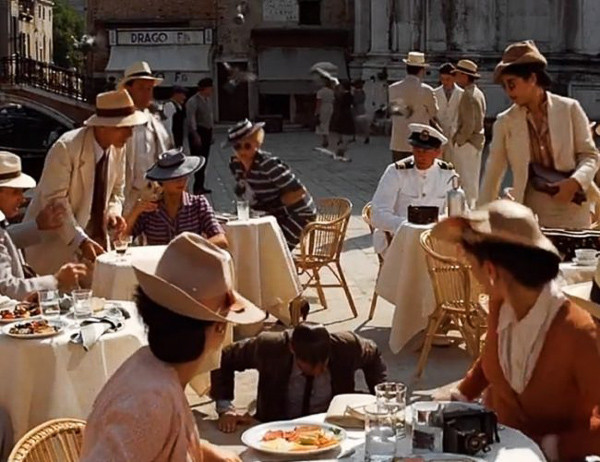 Indiana Jones emerge de una alcantarilla en medio de la plaza, para asombro de los elegantes clientes sentados en las mesas