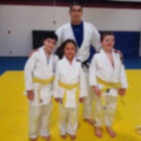 Sensei Josh Shannon with Judoka being graded for yellow belt