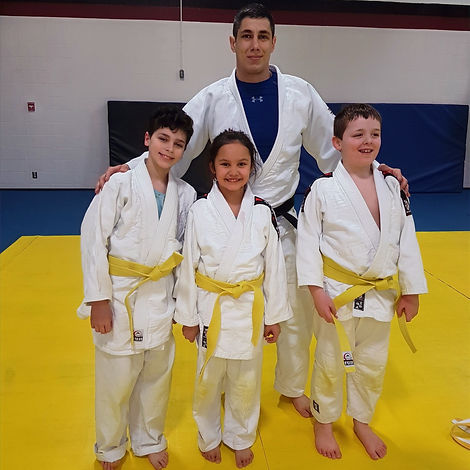 Sensei Josh Shannon with Judoka being graded for yellow belt