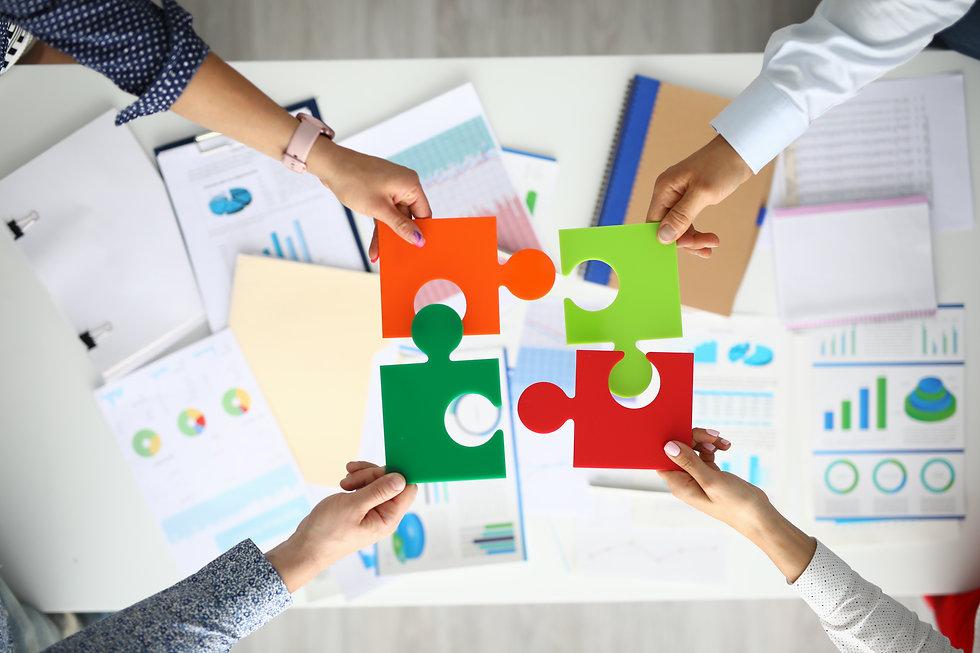 businessmen-hold-multicolored-puzzles-ha