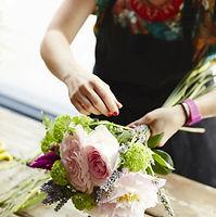 Mains blanches qui attachent un bouquet de fleurs roses