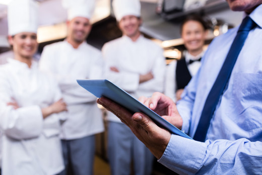 Mid section of restaurant manager using