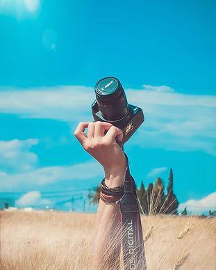 person-holding-black-canon-dslr-camera-k