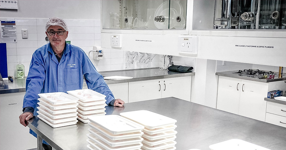 A man wearing a blue lab coat stands in an industrial laboratory kitchen what the hell four stacks of white trays on a steel bench in front of him