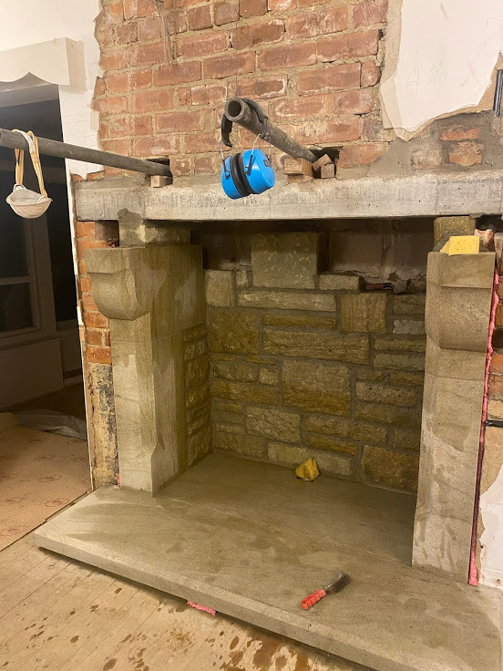 Hearths, jambs and corbels installed and the stone in the rear of the opening is being built up.