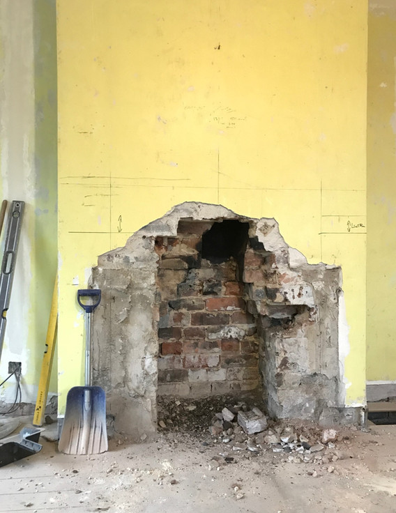 Making preparations for the new fire surround by creating a larger opening.