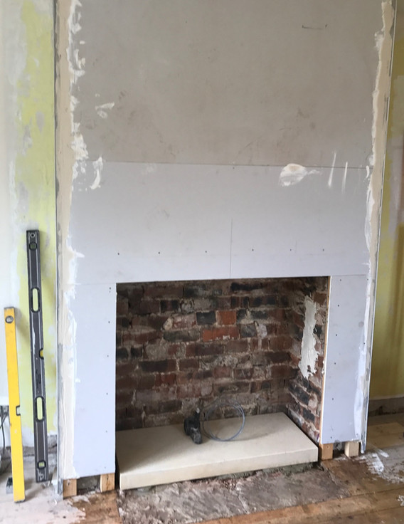 Chimney breast extended and plasterboard fixed.  Inner hearth goes down.
