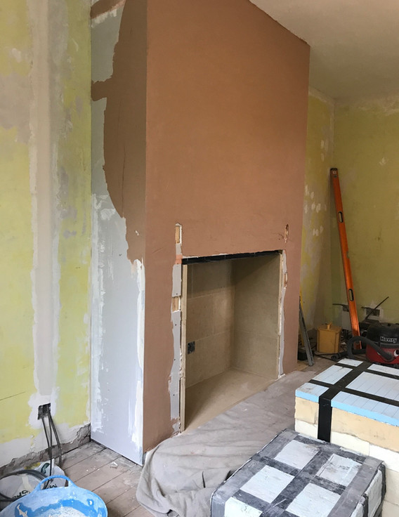 Chimney breast is plastered ready for the installation of the new fire surround.