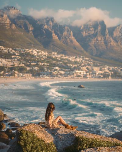 woman-sitting-on-rock-near-body-of-water