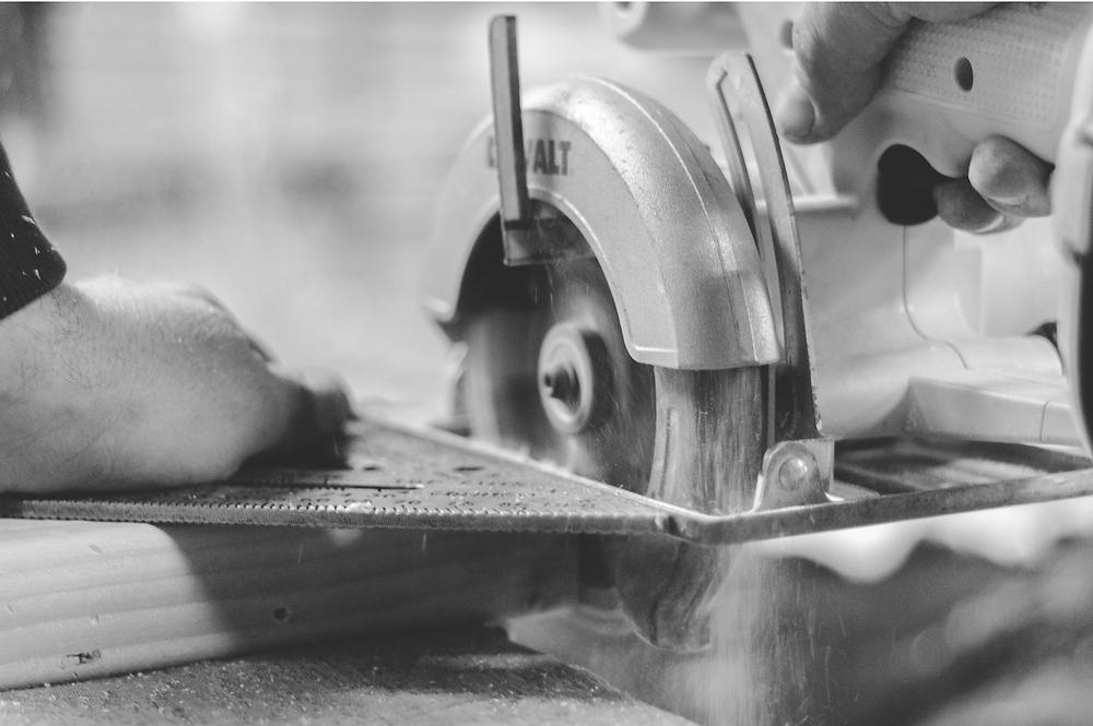 Handyman Cutting Wood with Saw