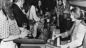 John Paul Jones of English rock group Led Zeppelin plays a Thomas electric organ behind the bar on board a private Boeing 720B airliner known as 'The Starship', which is being used by the band on their North American tour, 30th July 1973. (Photo by Daily Express/Hulton Archive/Getty Images)