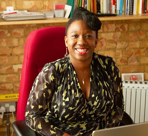 Ann-marie Idiagbonya  CEO of Creative Awakenings sitting in an office, wearing a yellow, grey and black dress.jpg