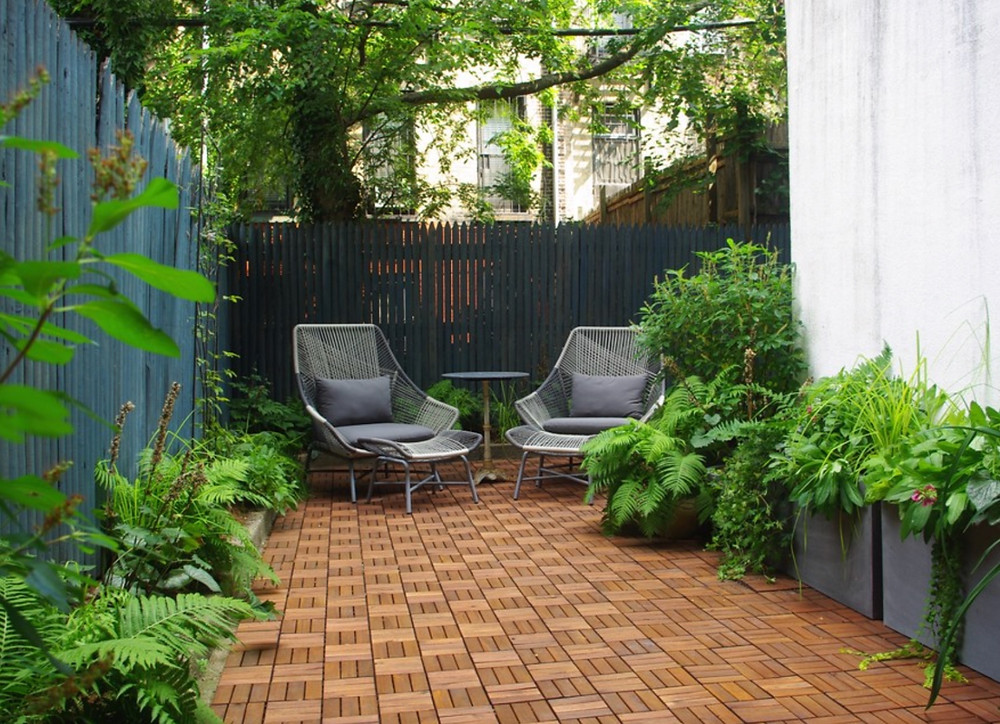 A Brooklyn backyard with wooden tile covering. Design by Staghorn NYC.