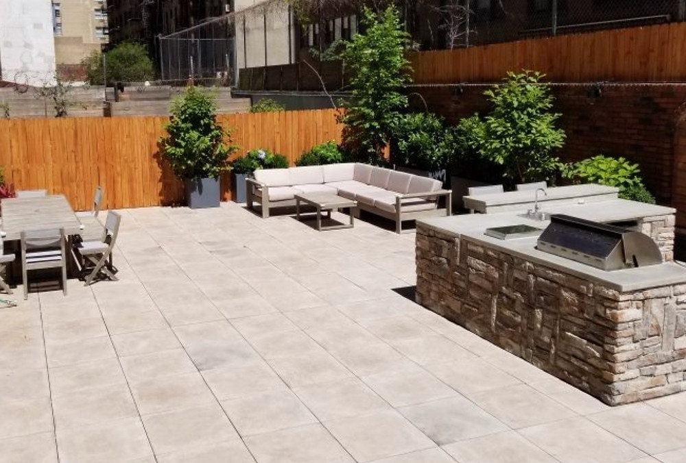 Porcelain pavers on a pedestal system combine well with other stone details like this backyard in Manhattan. Design by Staghorn NYC.