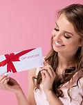 Beautiful woman giving a gift voucher .j