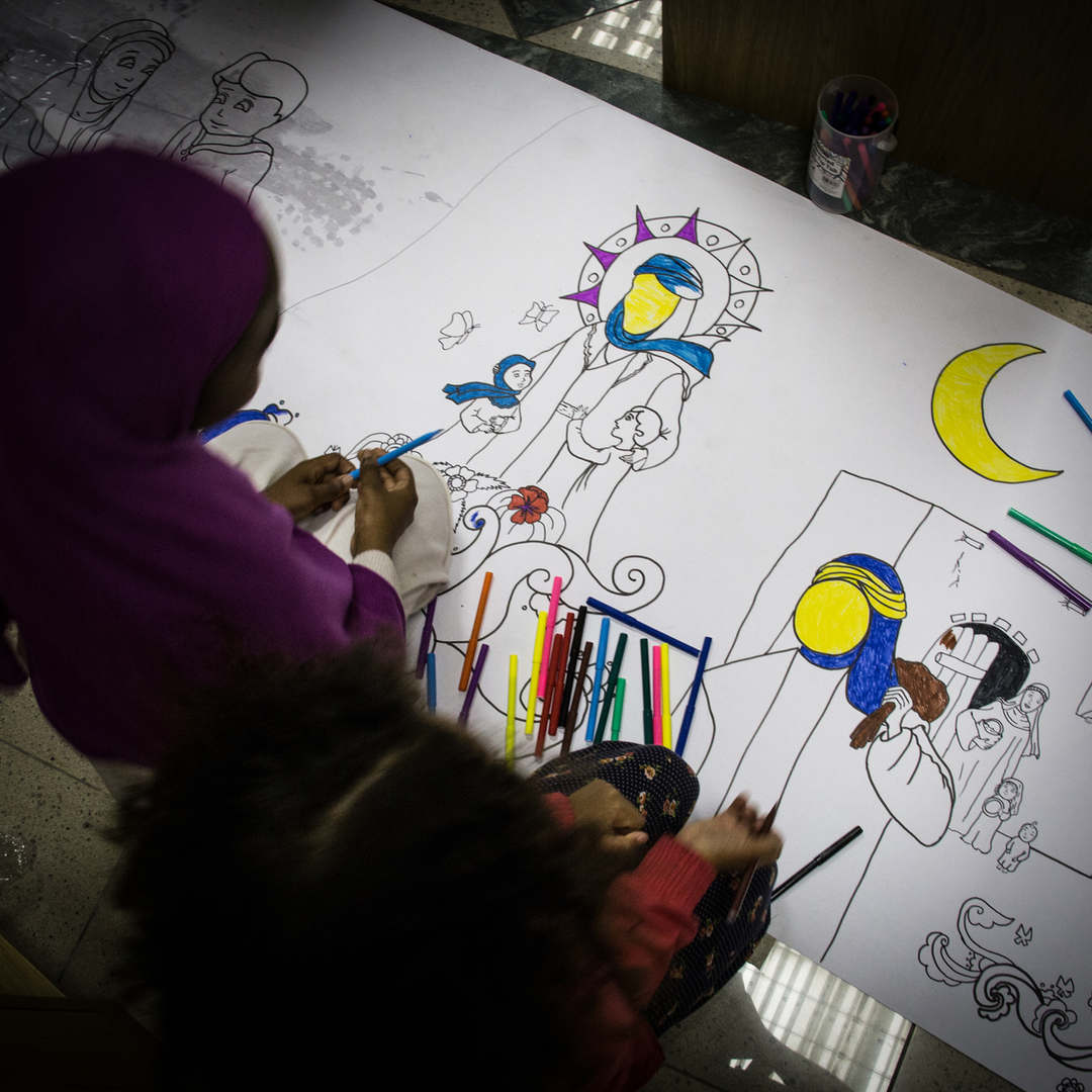 Two girls color a religious scene, during a meeting of the Ahlul Beit Community in London.