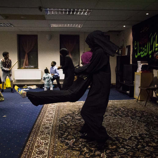 Two girls in their abayas and hijabs play, during a meeting of the Ahlul Beit Community.