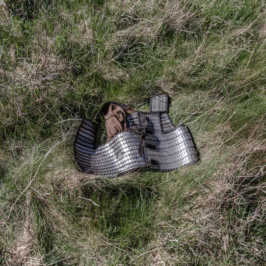 A piece of steel-plate armour lies in the grass, during a battle.