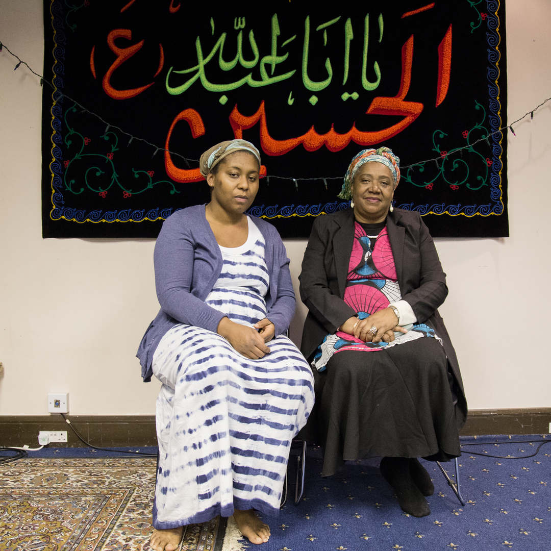 The wives of two members of the Ahlul Beit Community pose for a portrait, during a meeting.