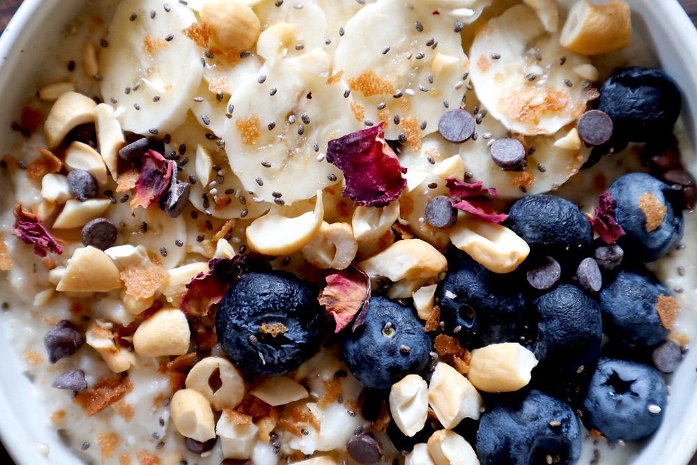 Creamy oatmeal with bananas, blueberries, chopped cashews, rose petal, chocolate chips, & coconut butter