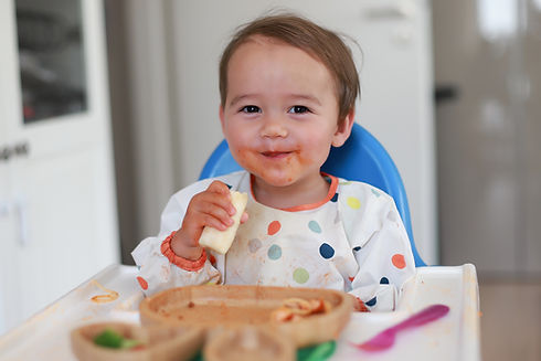 Happy smiling baby holding a slice of ba