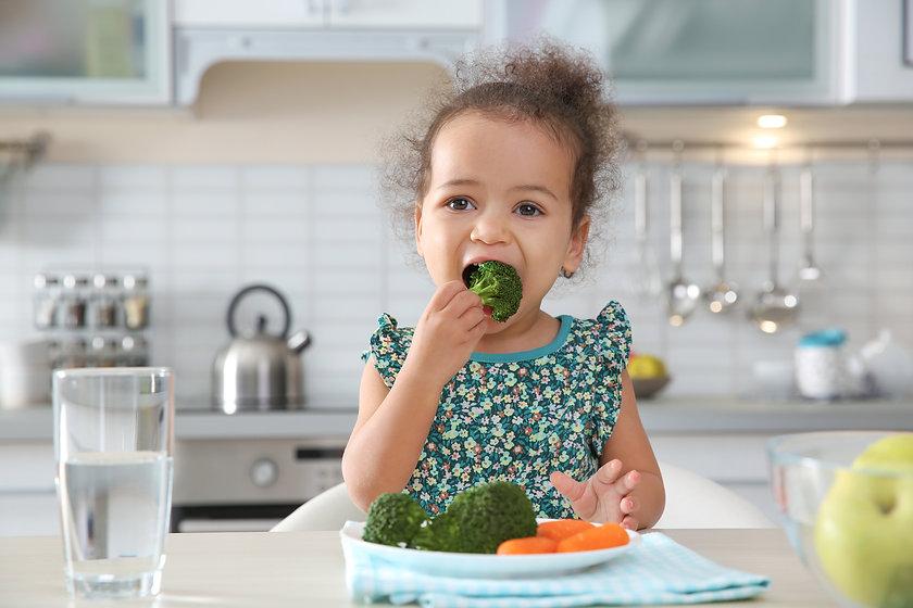 Cute African-American girl eating vegeta