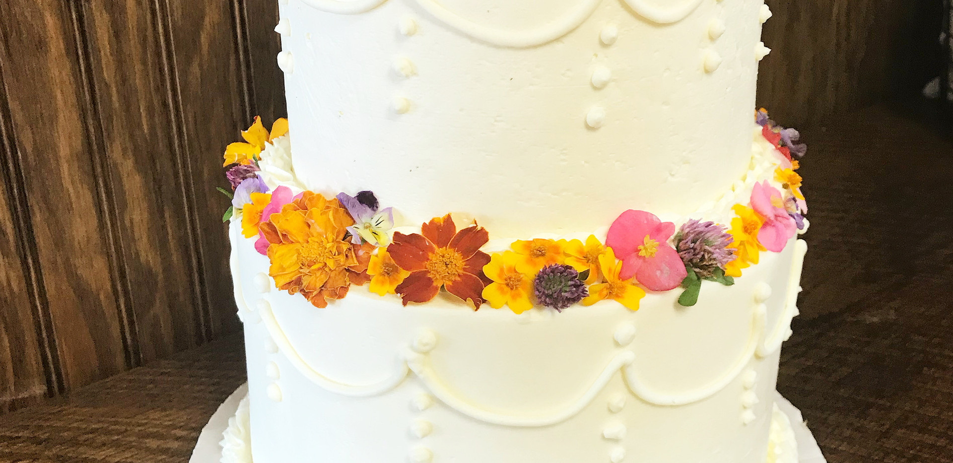 a two tier cake with fresh edible flowers